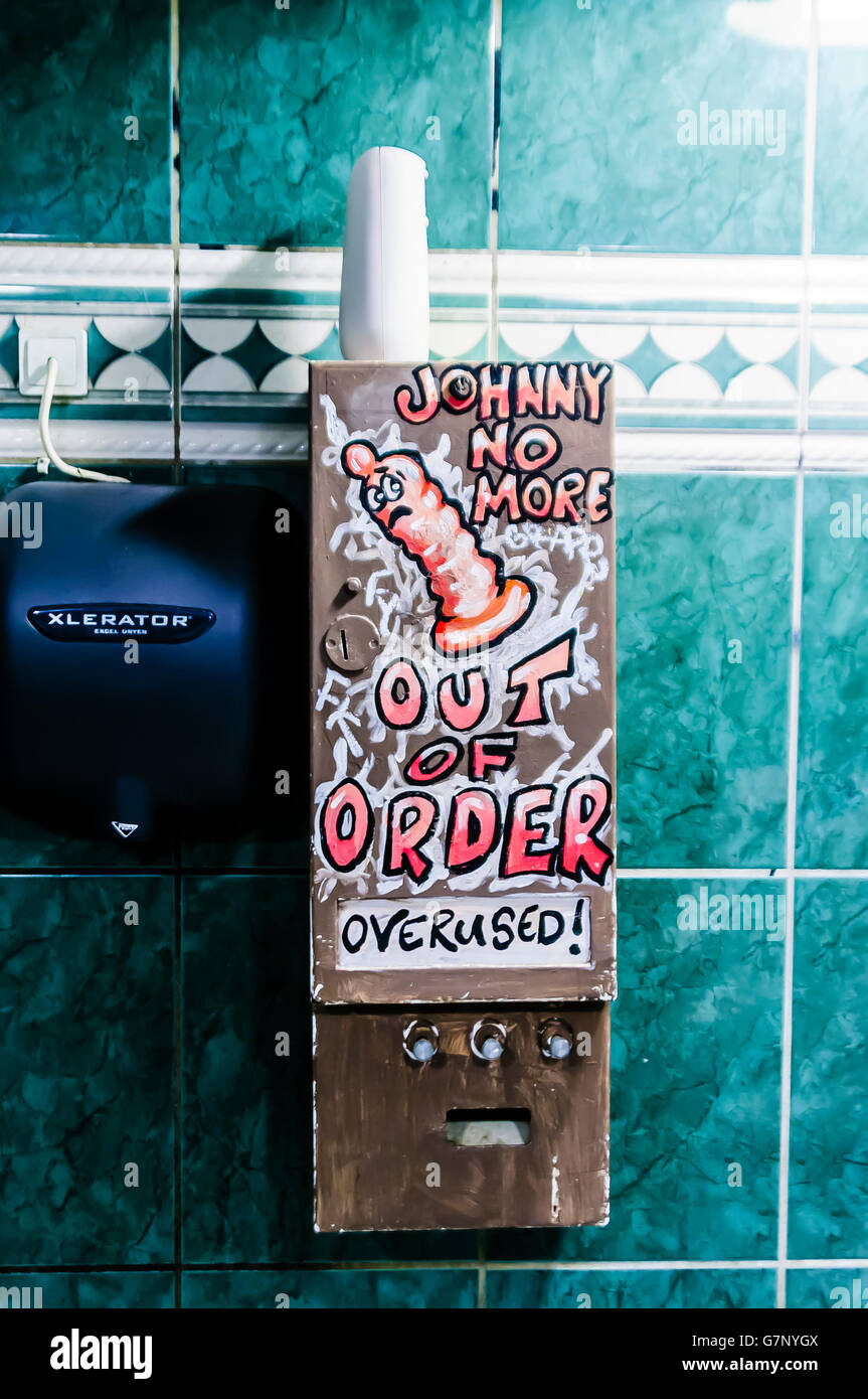 Broken condom machine in a gents' toilet saying 'Johnny no more.  Out of Order.  Overused'. - Stock Image