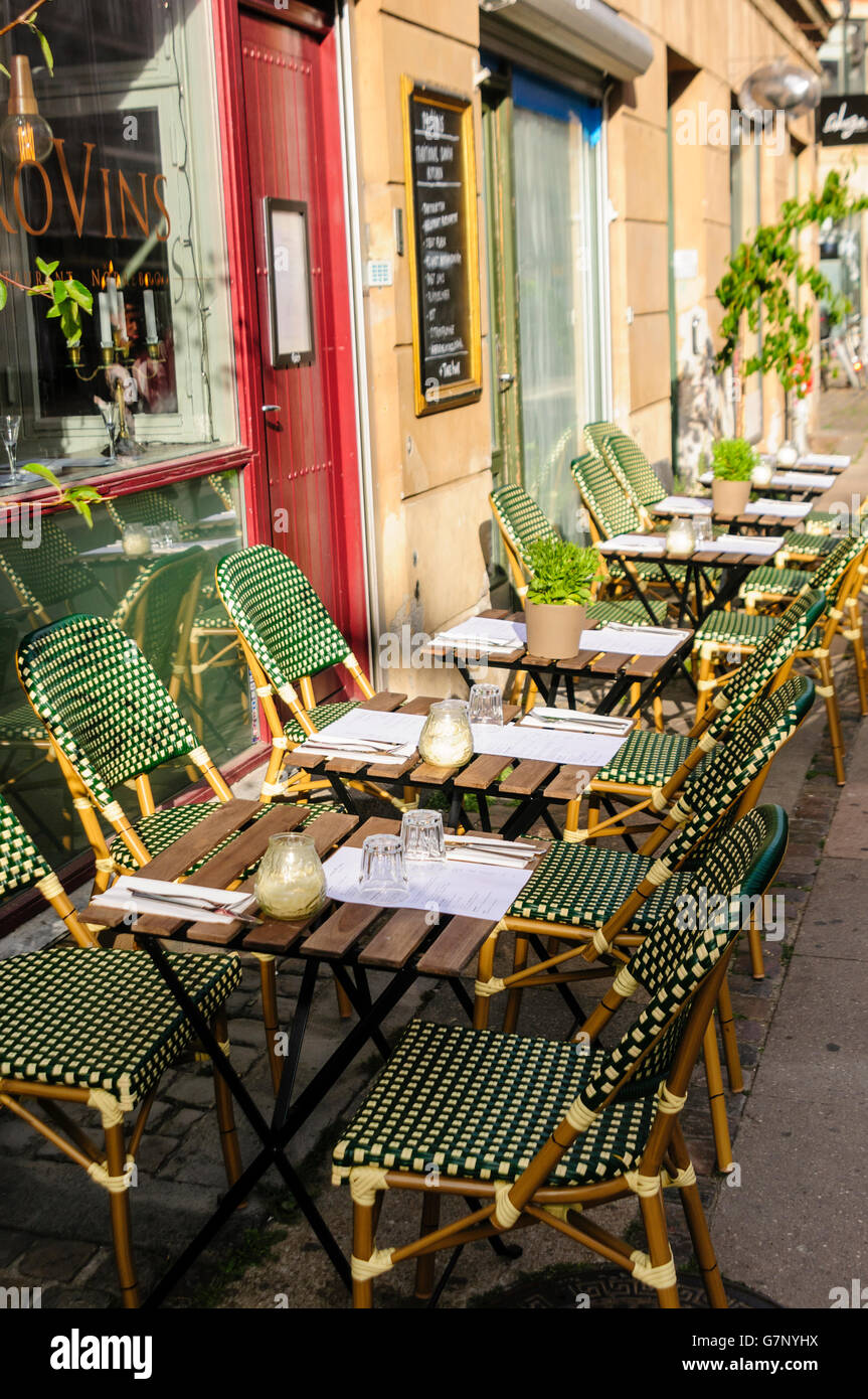 Tables arranged outside a restaurant in Copenhagen, Denmark for al-fresco dining - Stock Image