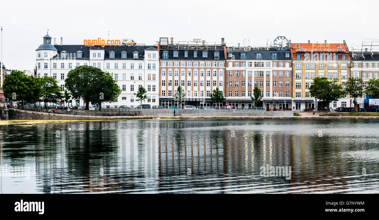 Buildings with neon advertising signs on the roofs beside the Sortedams Sø, Copenhagen - Stock Image