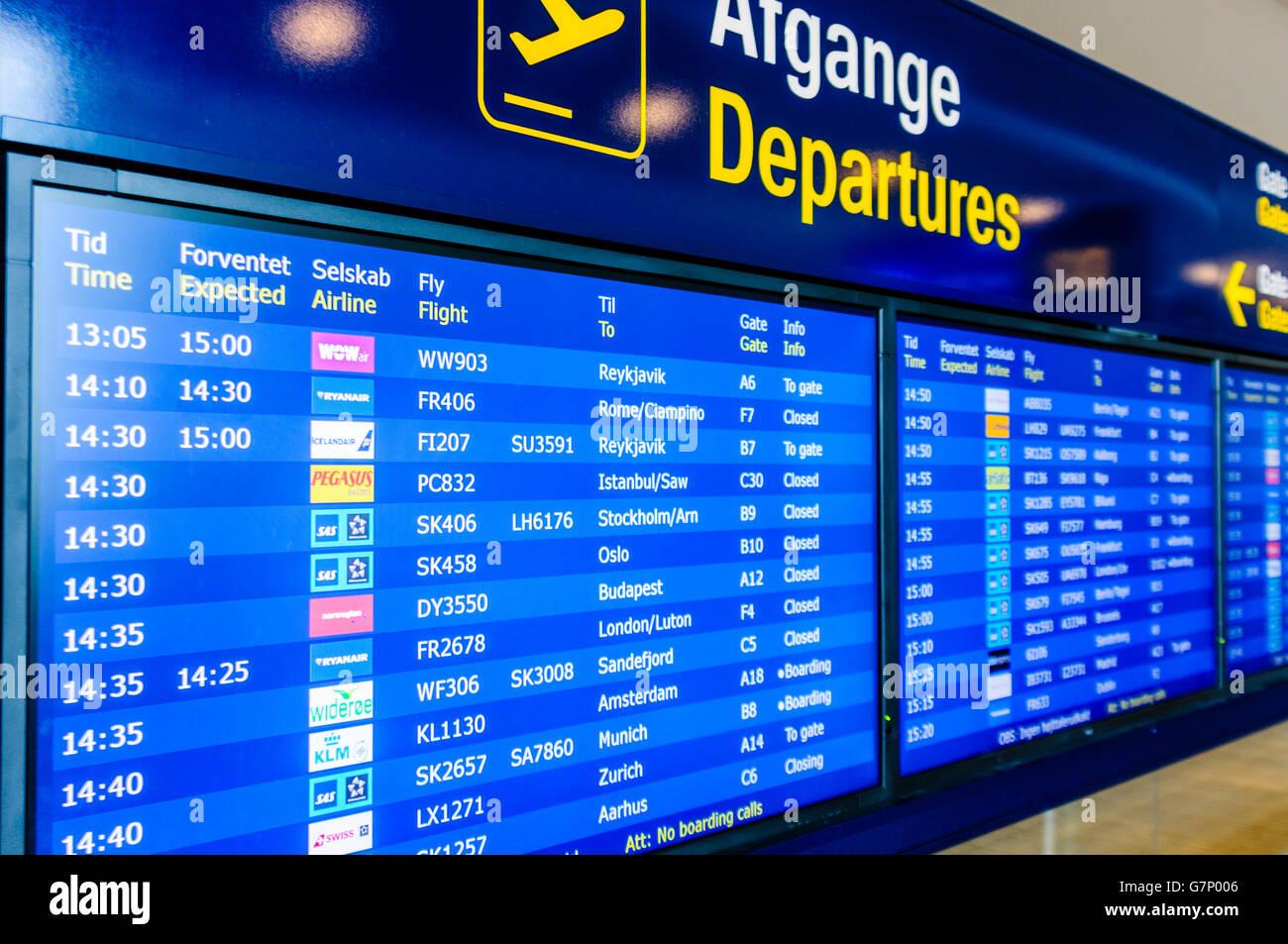 Departures board at Copenhagen Airport. - Stock Image
