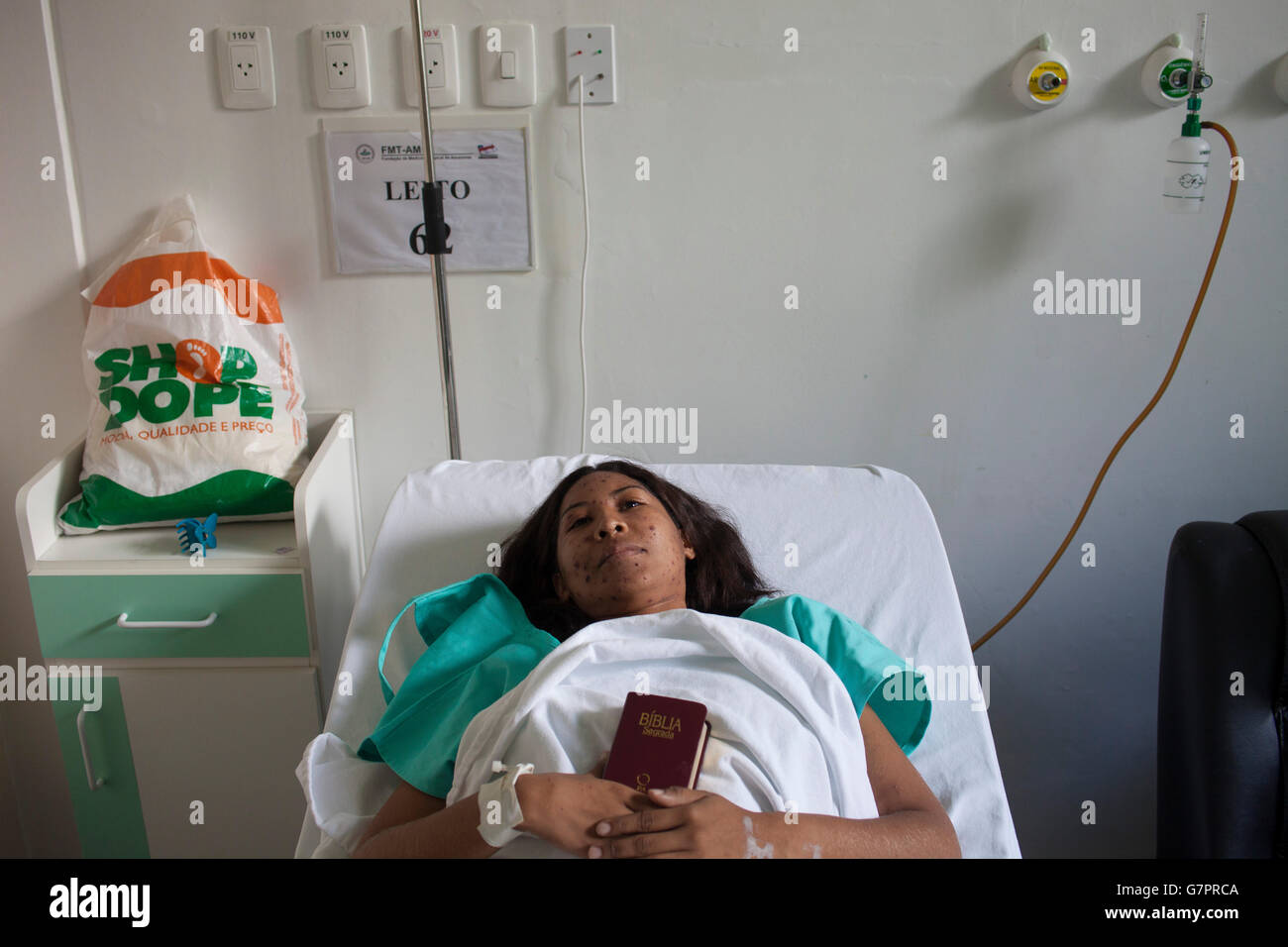 Hospital patient holds a Bible - measles, a highly contagious infection caused by the measles virus is an airborne - Stock Image