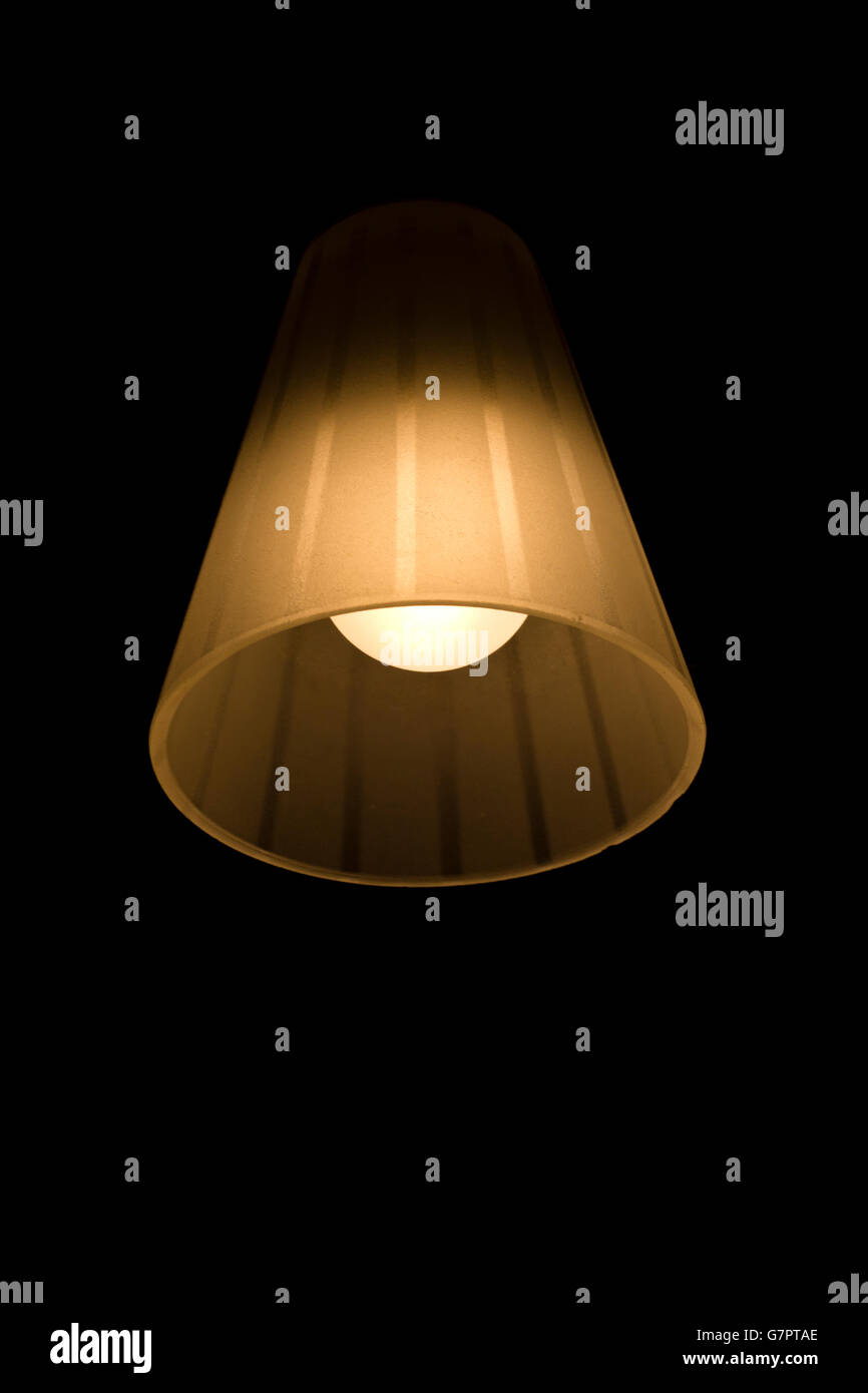 Lamp with bulb shining in the darkness. - Stock Image