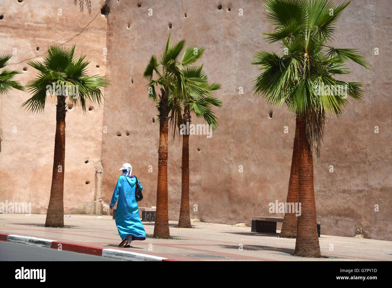 Woman in head cloth with unrecognizable face walking for city wall in Meknes - Stock Image
