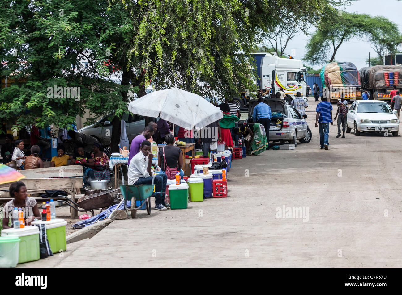 Soft drinks sellers and travellers at the border control area on the Zambian side of the Kazungula Fetty from Botswana. - Stock Image
