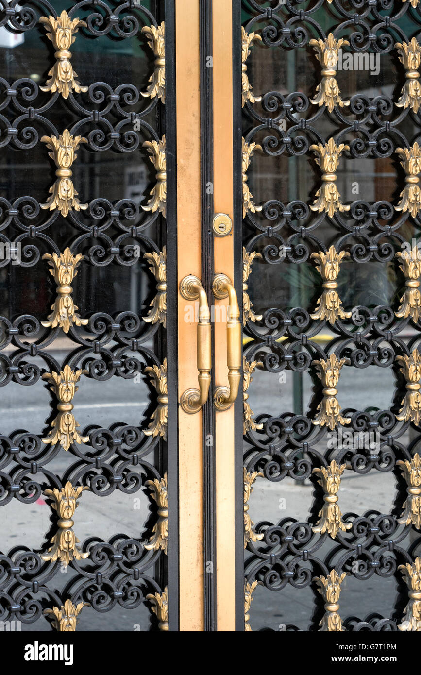 Close-up of Decorative Wrought Iron, Brass and Glass Double Doors and Handles.  Manhattan, New York City. - Stock Image