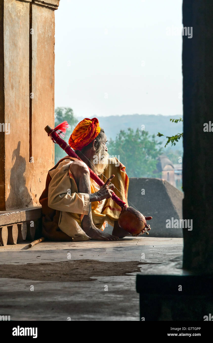 Unidentified Indian Sadhu sitting and playing the tumbi at window of Chaturbhuj Temple - Stock Image