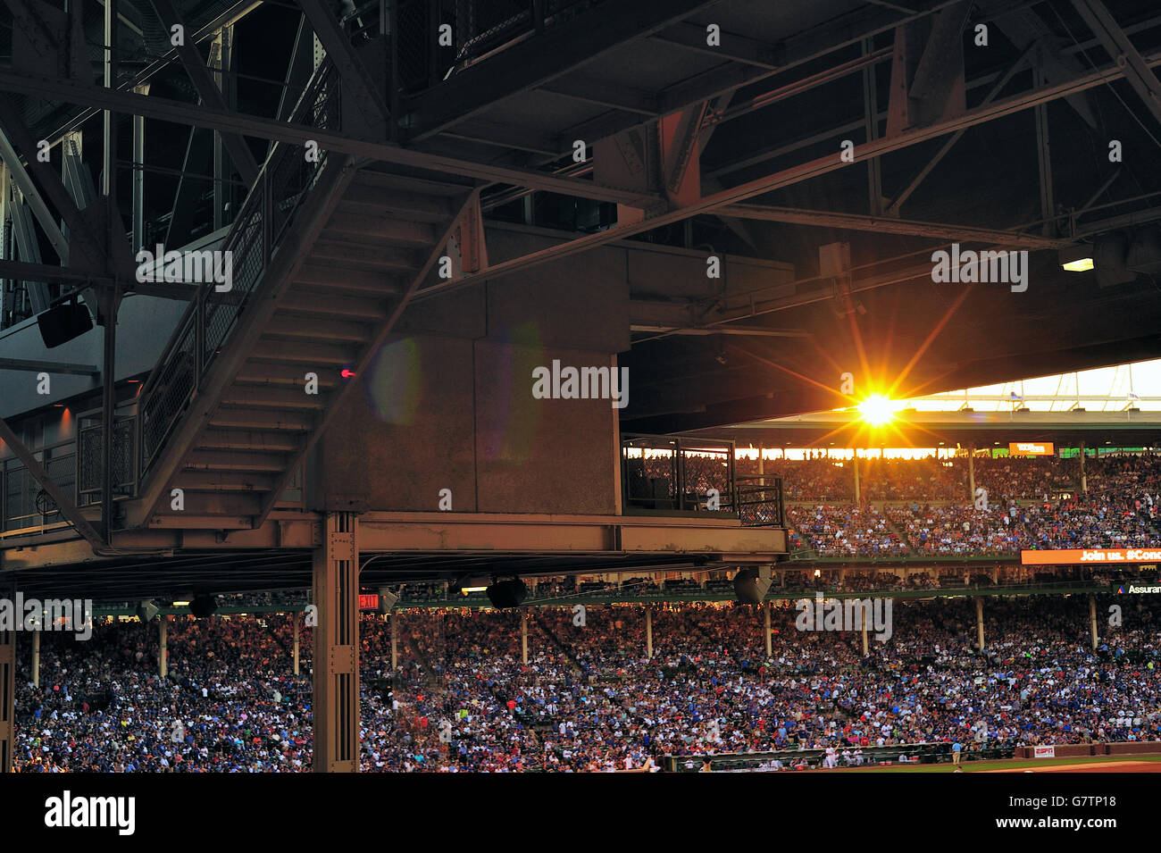 Game day at Wrigley Field, home to the Chicago Cubs as the setting sun creates a burst between the levels of the - Stock Image