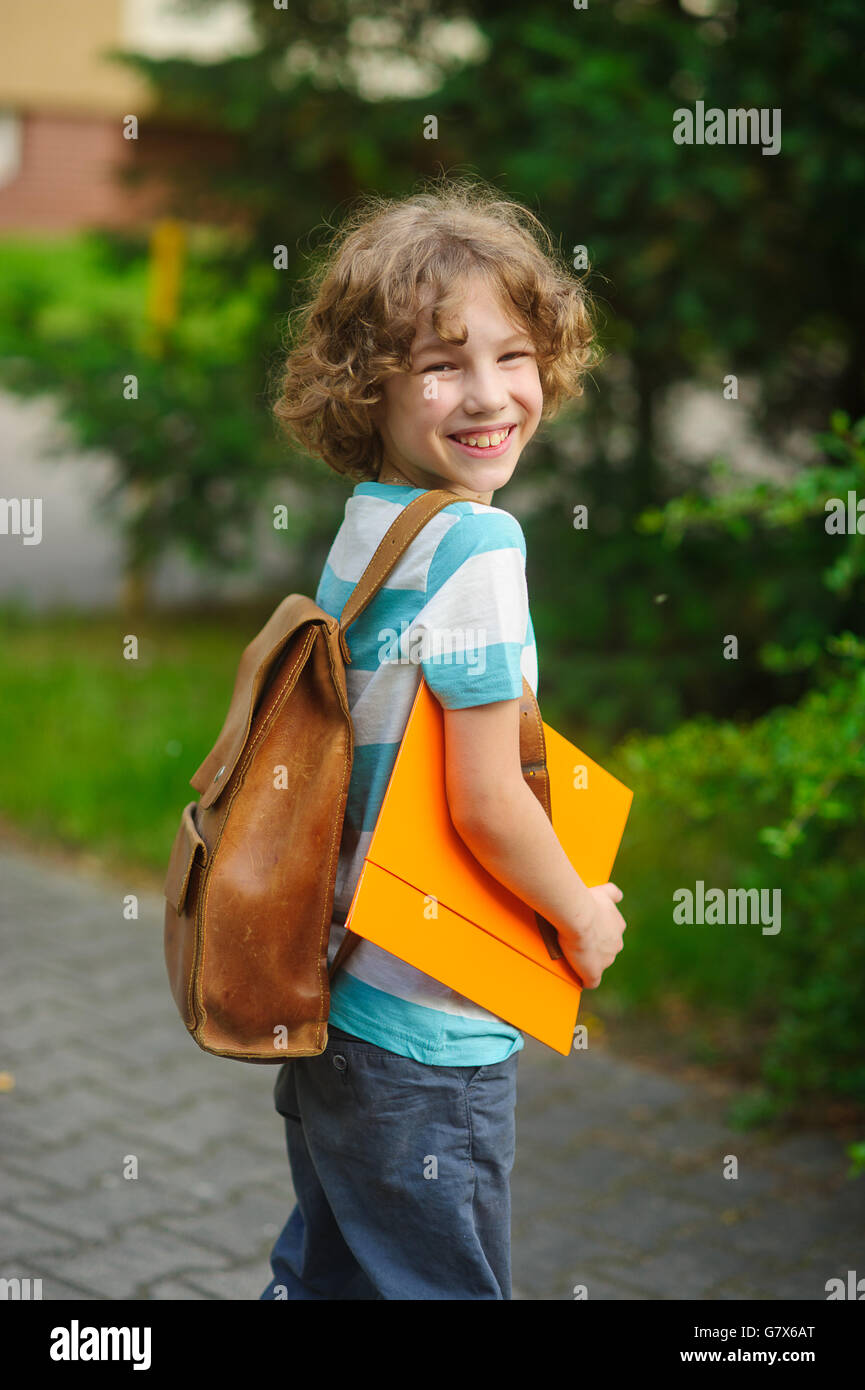 The pupil of elementary school on a schoolyard. The school student costs in a half-turn to the camera and smiles. - Stock Image