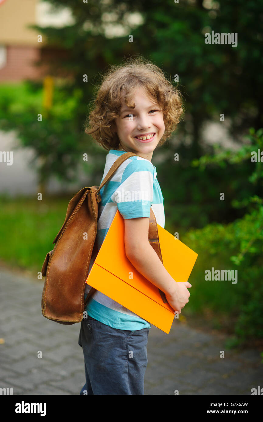 Cheerful school student on a schoolyard. The curly boy with a nice face. Behind the school student's shoulders - Stock Image
