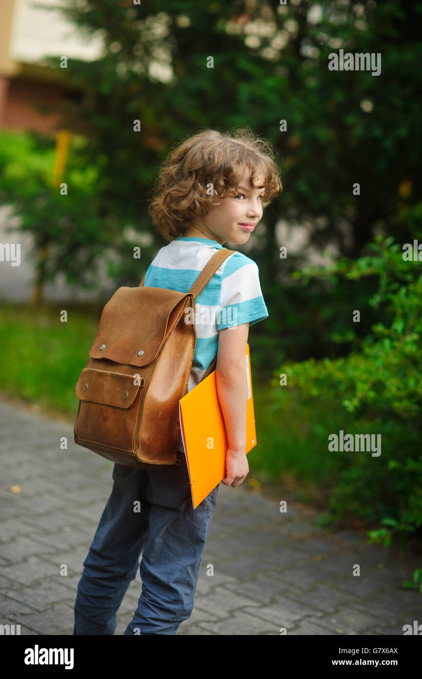 Little schoolboy with a school backpack behind the back. The school student stand in a half-turn to the camera. - Stock Image