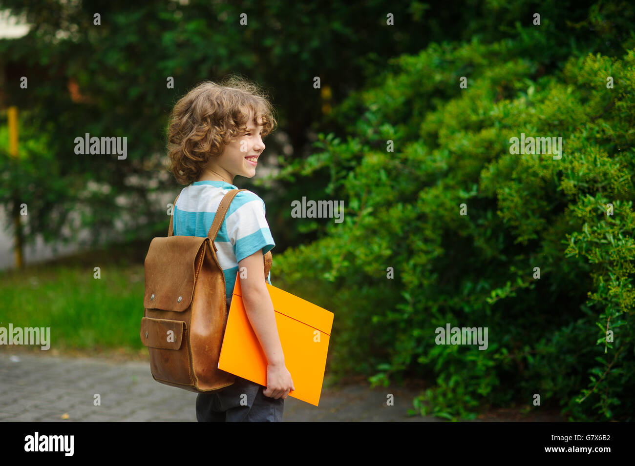 Chappy on a schoolyard. The school student stand in a half-turn to the camera. He looks in a distance and smiles. - Stock Image