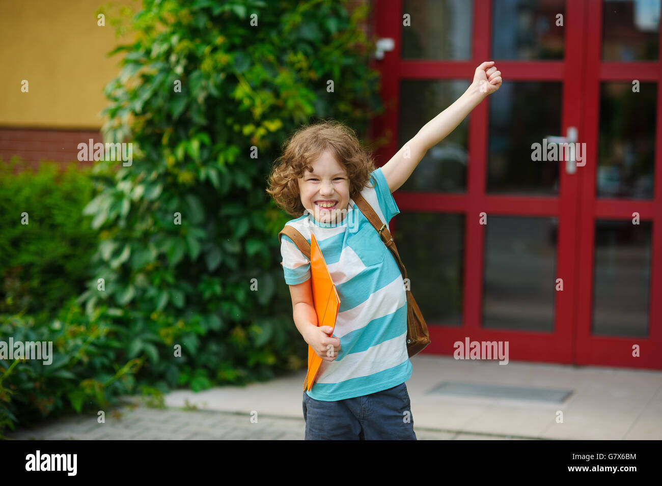 The schoolboy rejoices to the termination of academic year and the beginning of summer vacation. The boy has raised - Stock Image