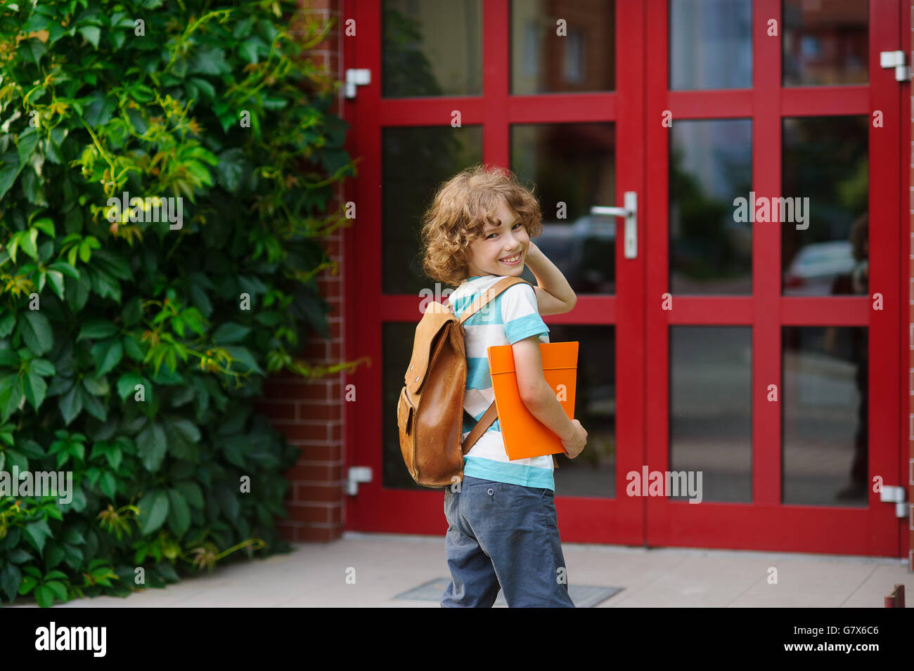 The joyful schoolboy has looked back near a school door. Behind shoulders at the pupil a satchel, in hands the bright - Stock Image