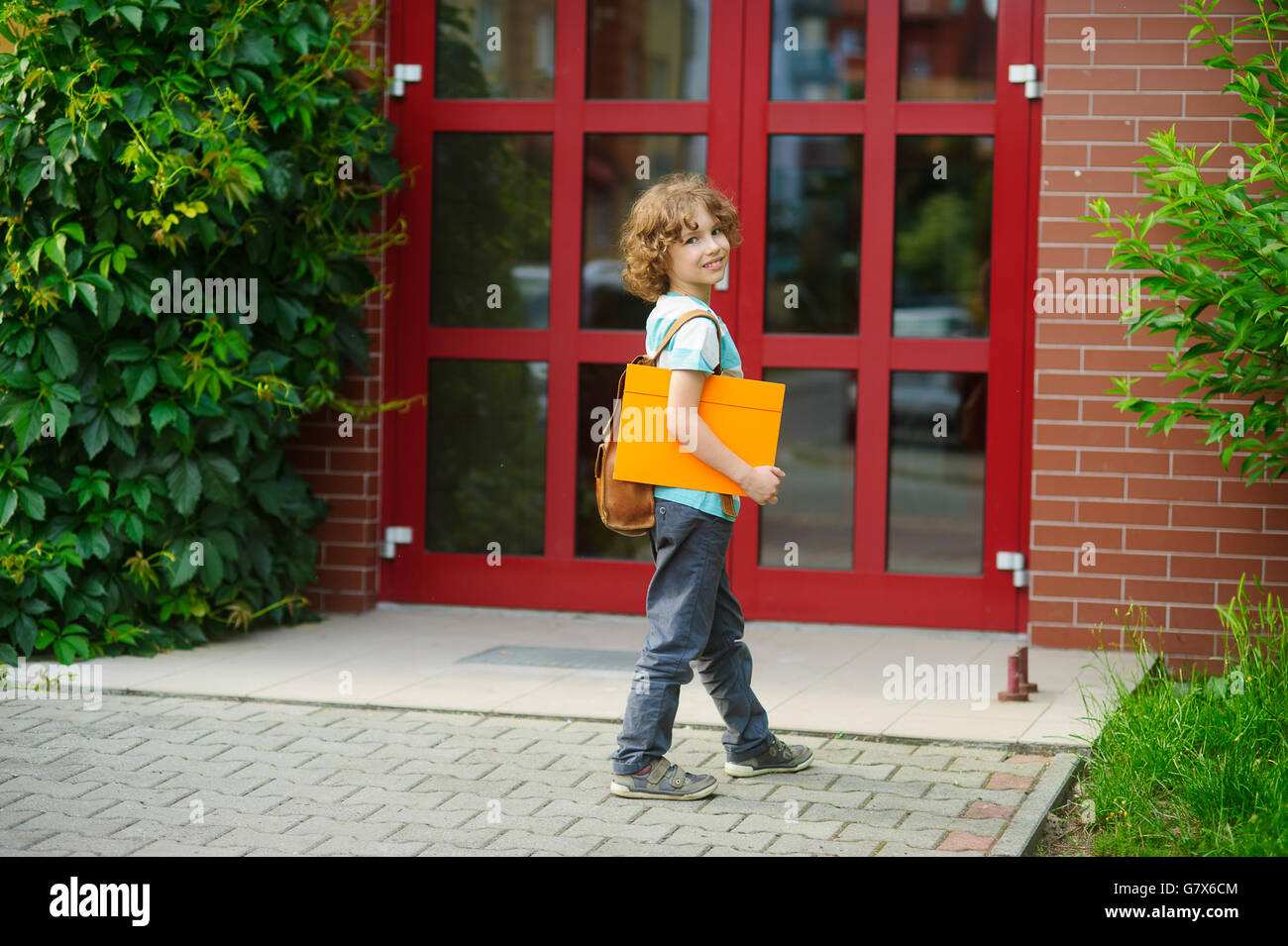 Cheerful first grader coming to the school door. Behind shoulders at the pupil a satchel, in hands the bright folder. - Stock Image