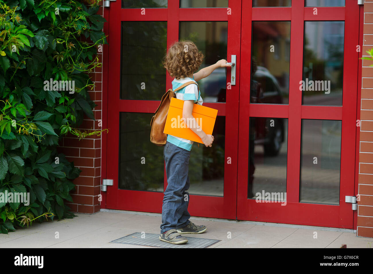 The little first grader opens a door of school. Behind shoulders at the pupil a school backpack, in hands the bright - Stock Image