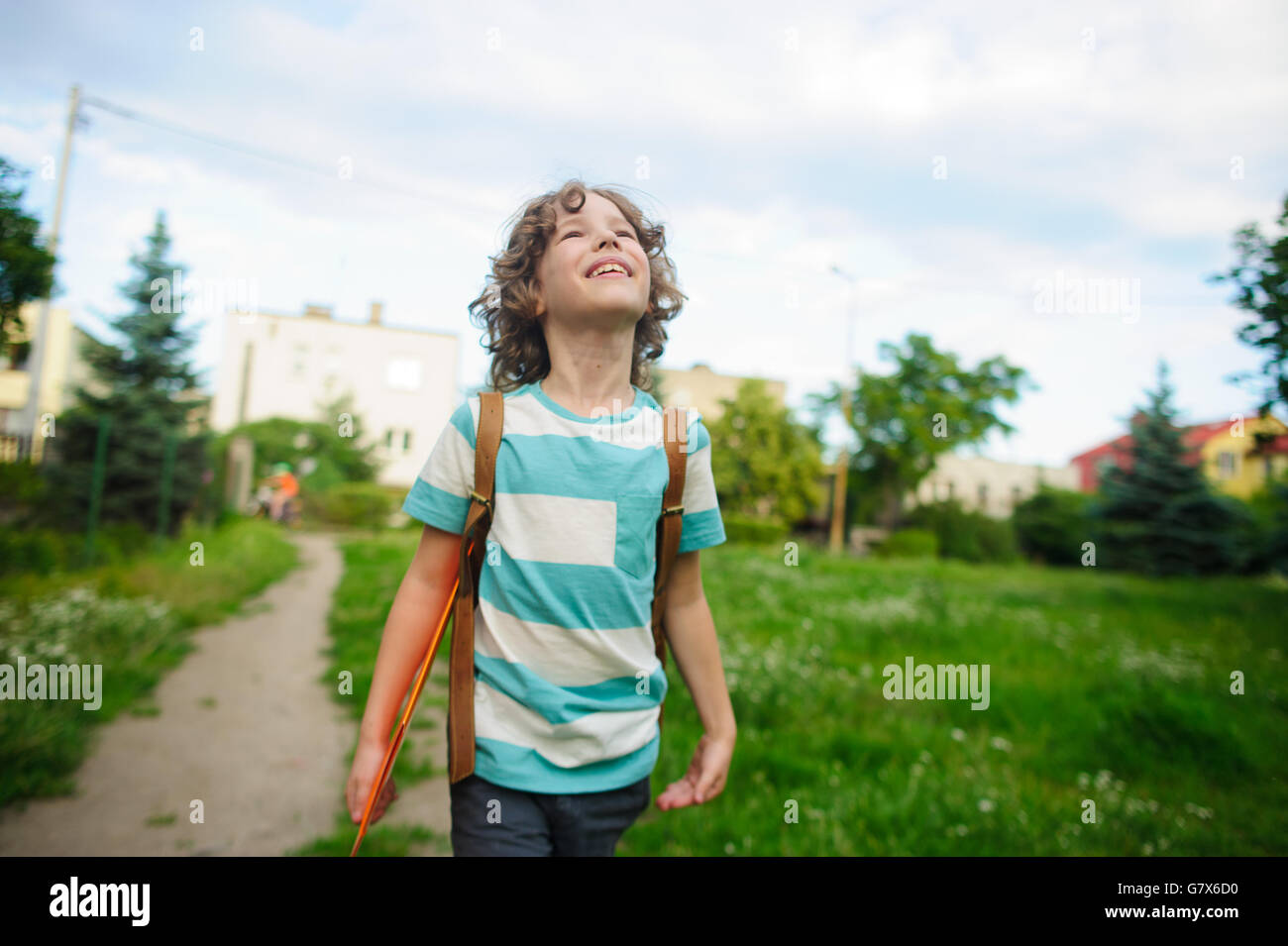 The school student comes back from school in good mood. The boy goes on a footpath. He has raised eyes to the sky - Stock Image