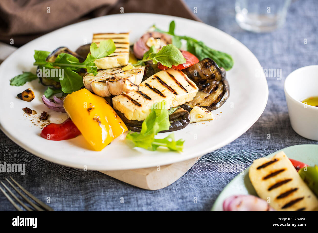 Grilled Halloumi with aubergine,pepper garlic and rocket salad - Stock Image