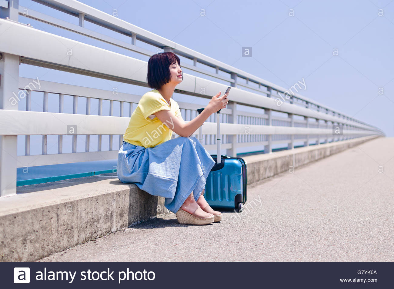 Woman sitting and operating smart phone - Stock Image