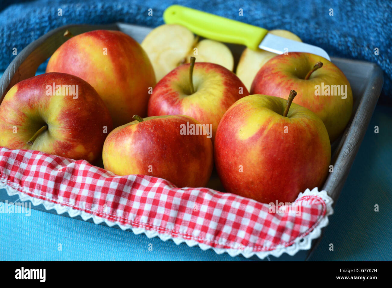 close up of red, yellow ,green apples in wooden bowl with knife and apple slices red white nostalgic countryside - Stock Image