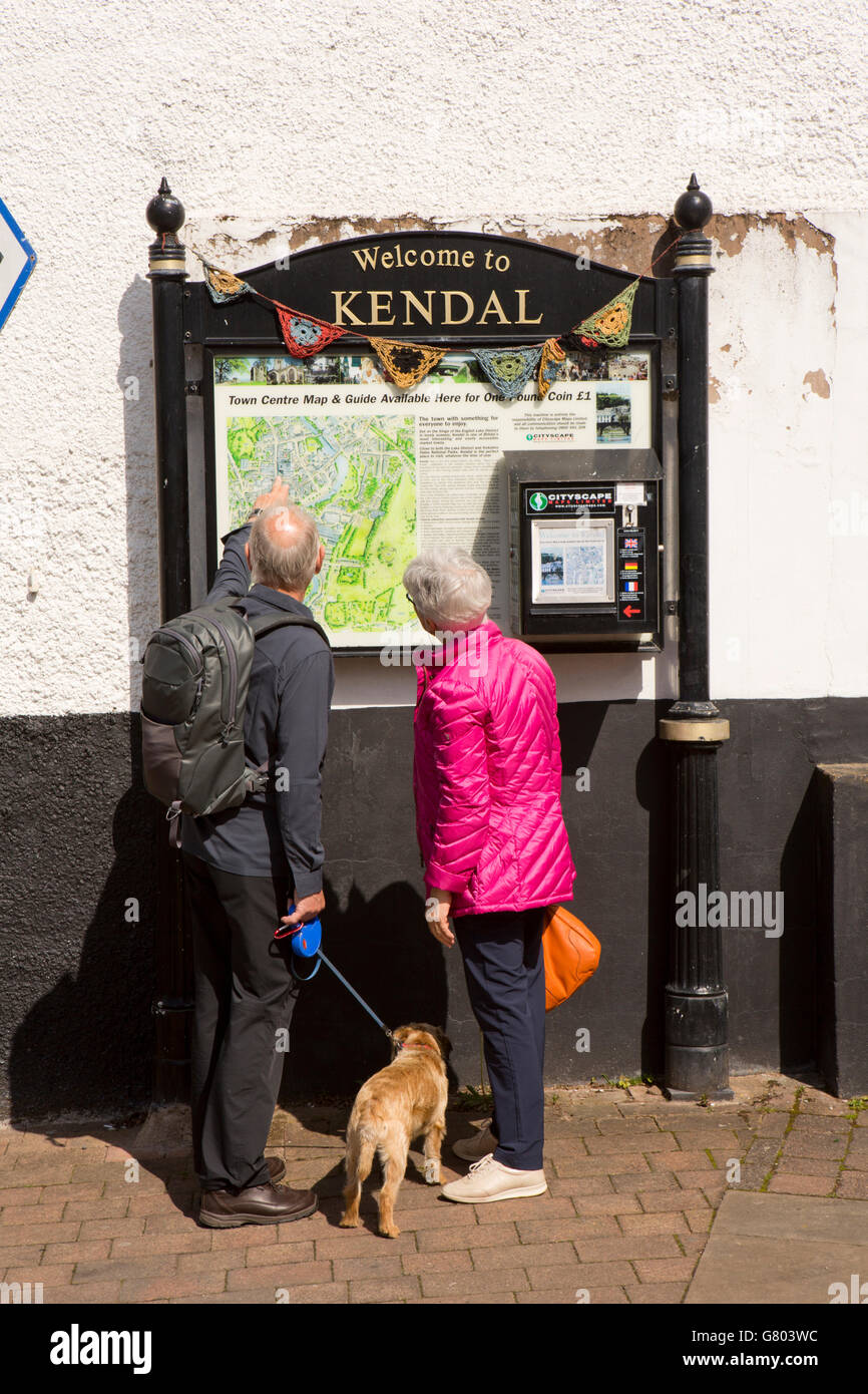 UK, Cumbria, Kendal, Finkle Street, older tourist couple looking at Welcome To Kendal, tourist information map - Stock Image