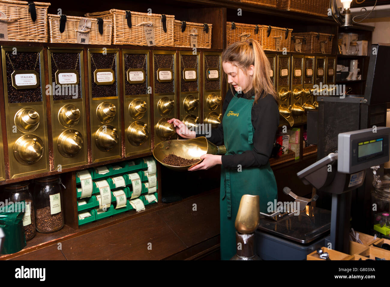 UK, Cumbria, Kendal, Stricklandgate, Farrers Coffee Merchants, assistant weighing beans - Stock Image