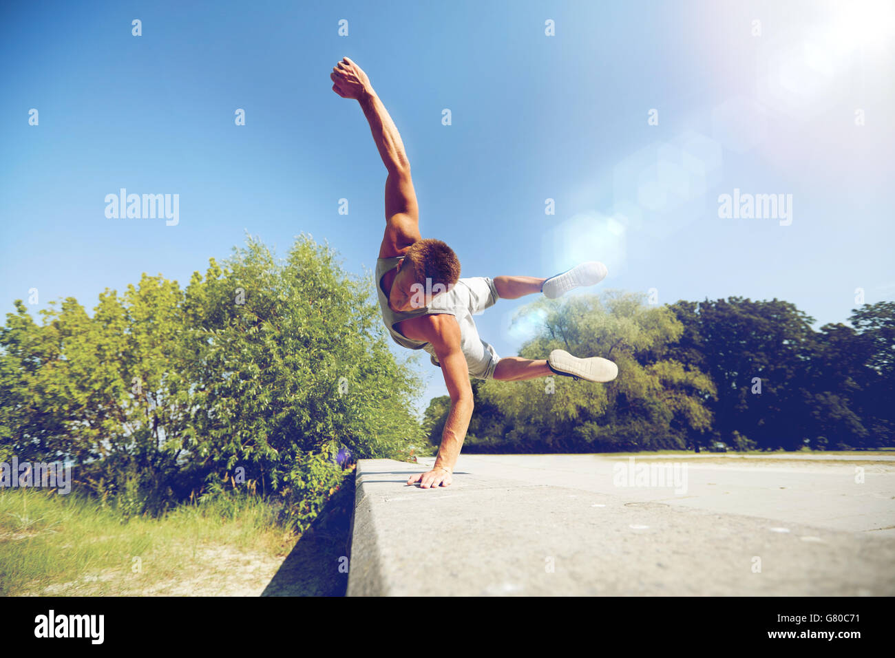 sporty young man jumping in summer park - Stock Image