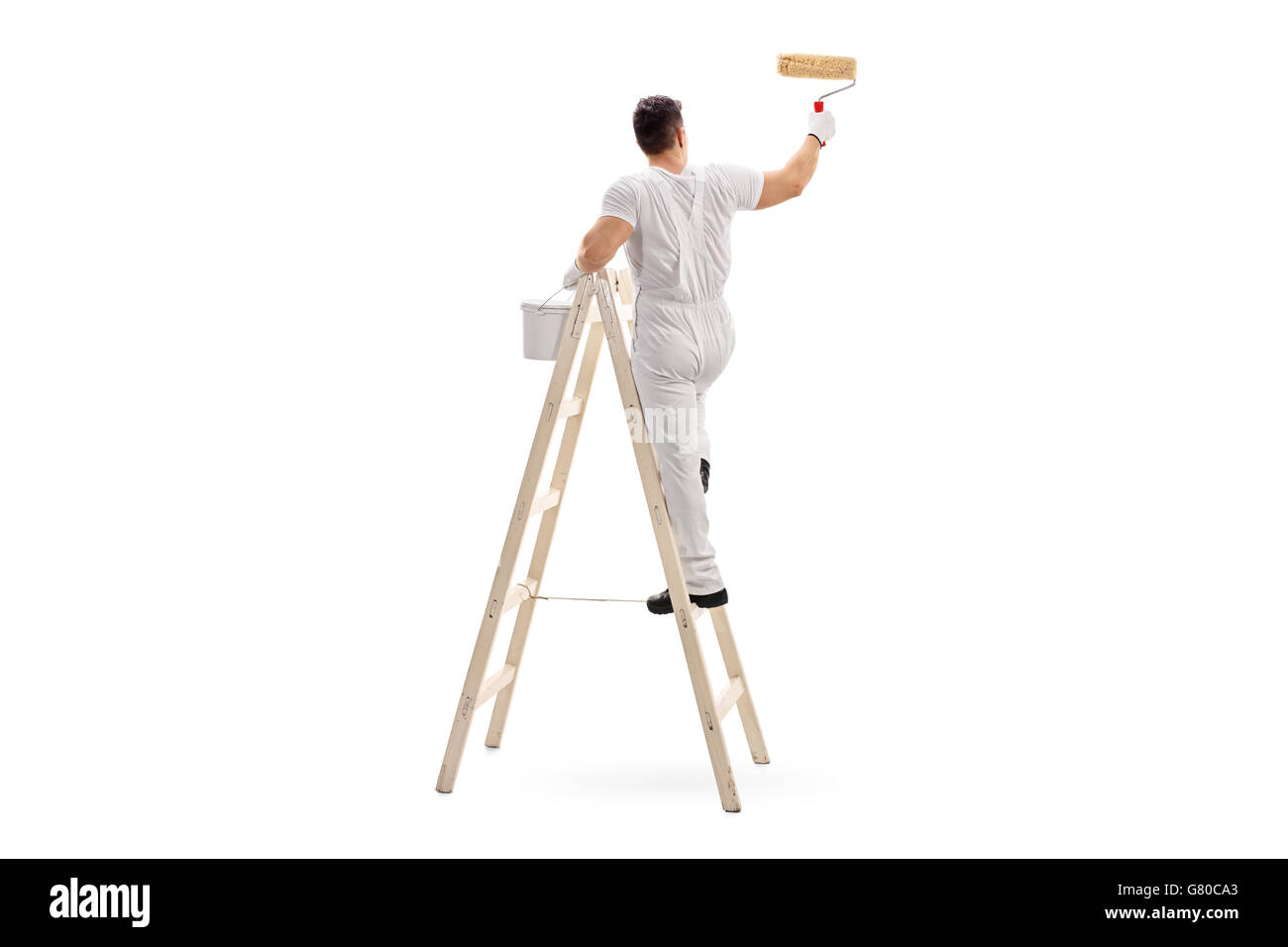 Young male decorator painting with a paint roller climbed up a ladder isolated on white background - Stock Image