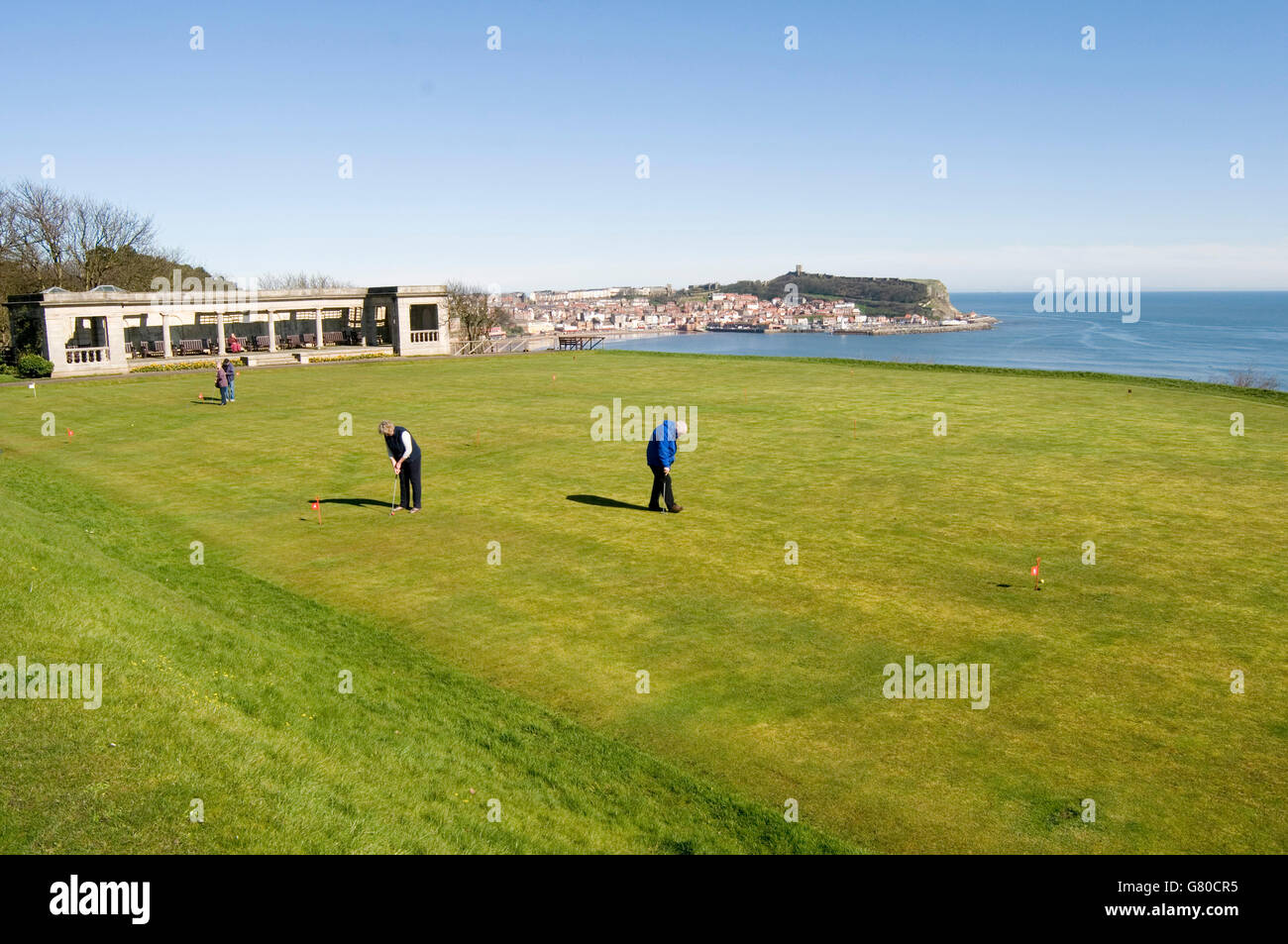 golf course courses putt putting green greens pitch and Scarborough bay north yorkshire sea north uk grass seaside - Stock Image