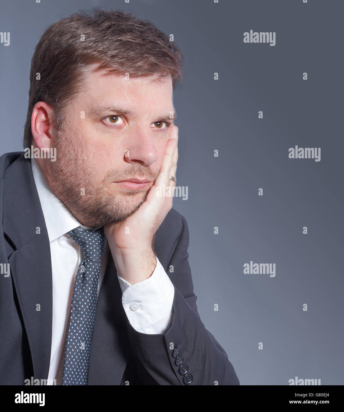 Business man worried about financial plan isolated on grey background - Stock Image