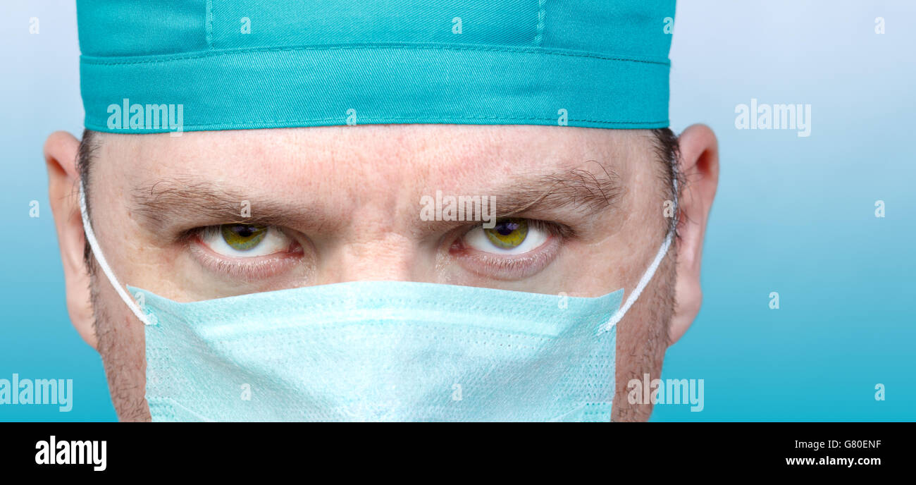 Adult male doctor portrait close up on blue background - Stock Image