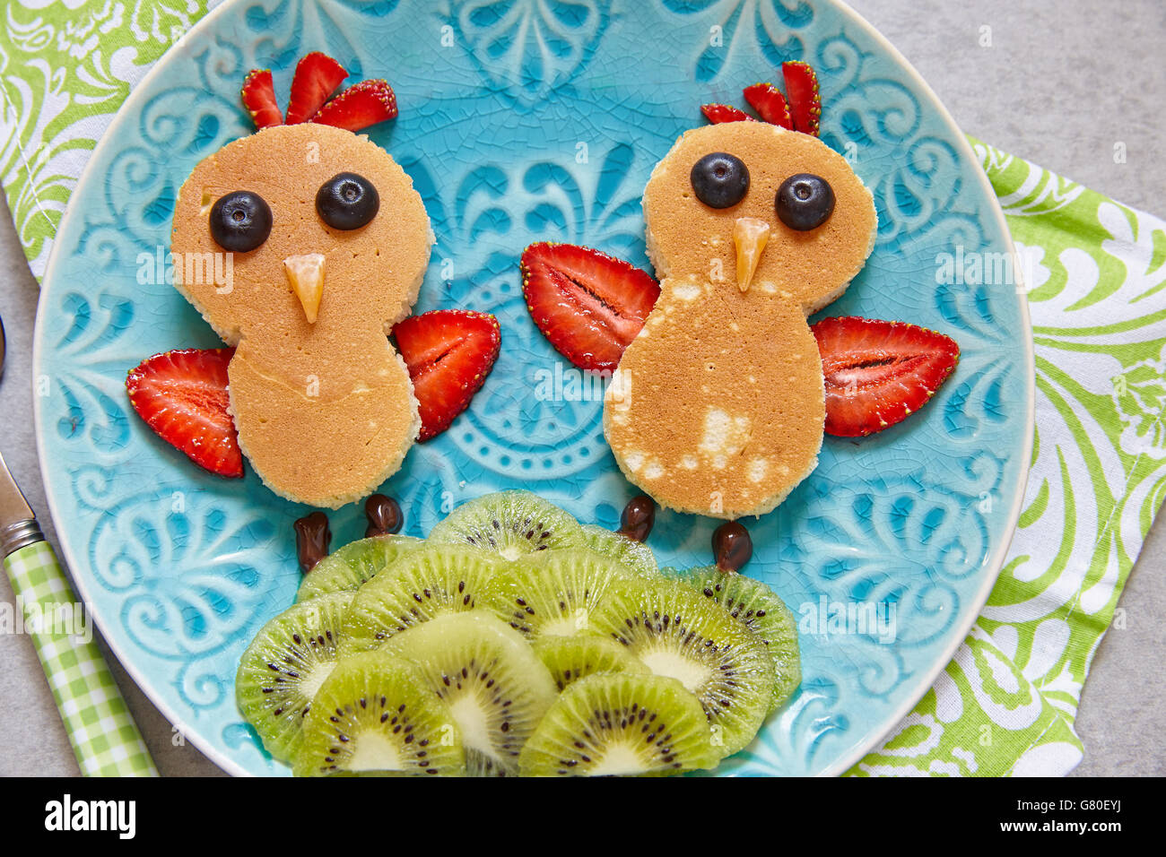 Funny chickens pancakes with berries for kids breakfast - Stock Image