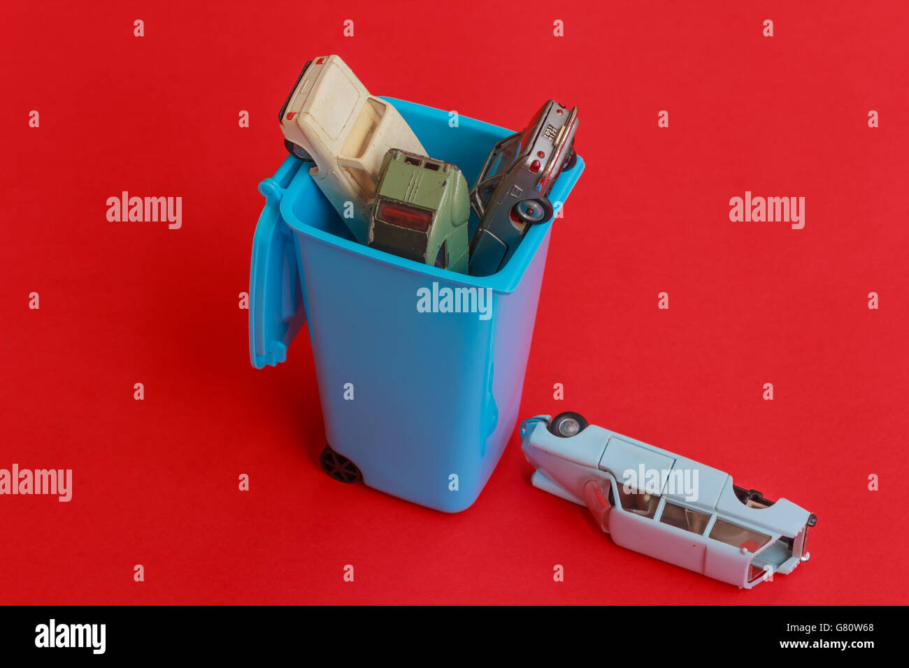 a garbage can inside with four cars that need to be scrapped - Stock Image