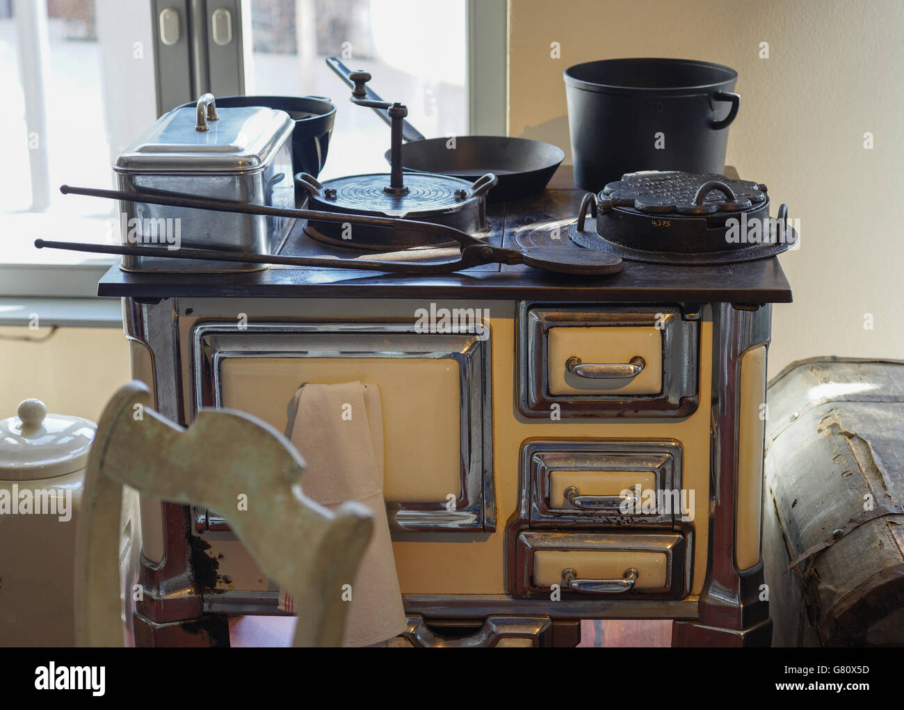 Old kitchen stove with cooking and baking utensils - Stock Image