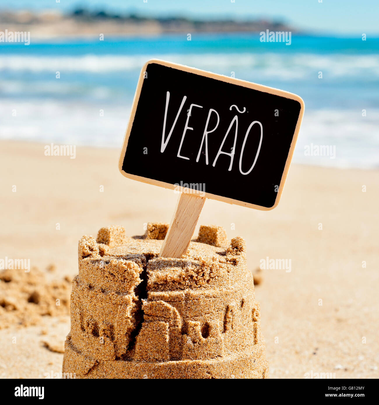 closeup of a sandcastle on the sand of a beach topped with a black signboard with the text verao, summer in Portuguese Stock Photo