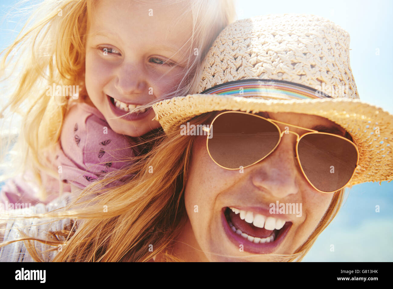 Laughing young mother in a trendy hat and sunglasses giving her little daughter a piggy back outdoors in the summer - Stock Image