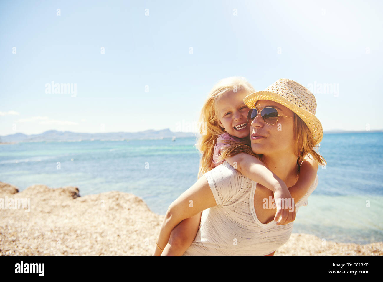 Laughing vivacious little blond girl with her mother at the beach riding on her in a piggy back on a rocky shore, - Stock Image
