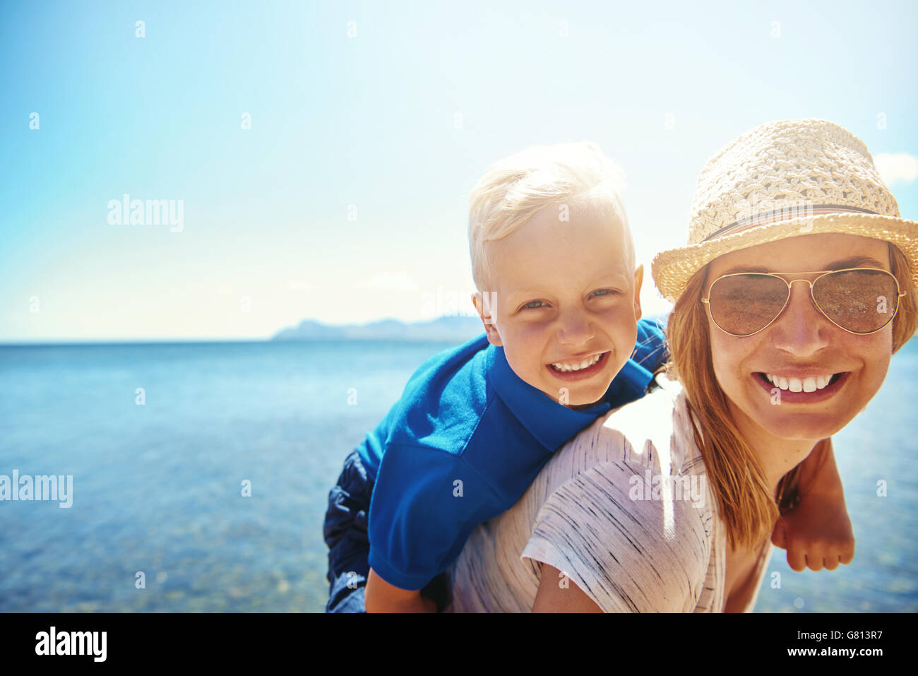 Happy little boy getting a piggy back ride from his attractive smiling mother in sunhat and sunglasses as they relax - Stock Image
