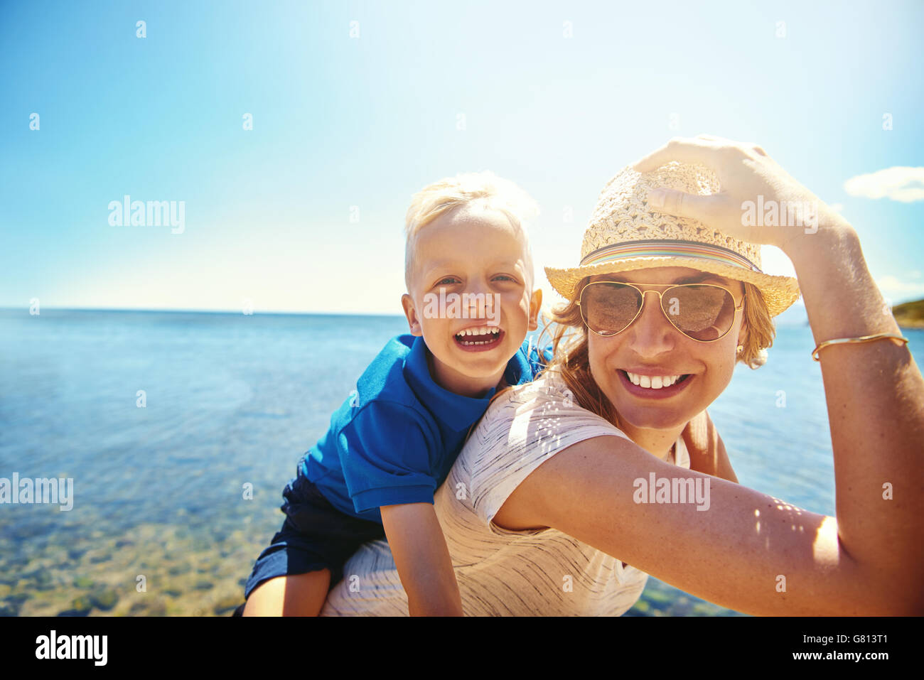 Happy young mother and son on a tropical beach with the laughing little boy getting a piggy back ride on her back Stock Photo