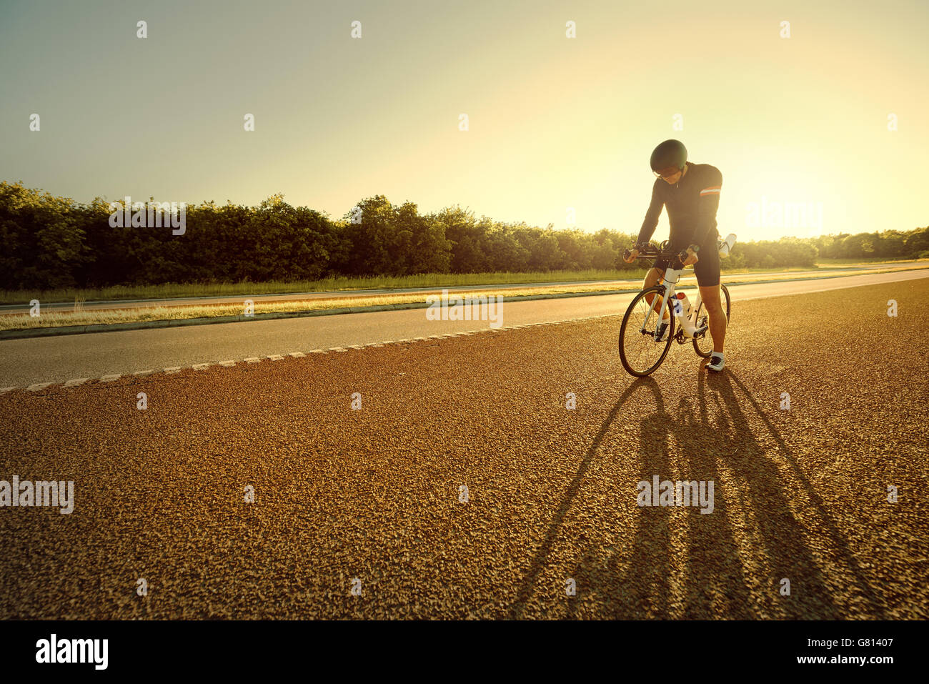 Single bicyclist wearing shorts, safety helmet and long sleeve jacket pausing at highway with long shadows extending - Stock Image