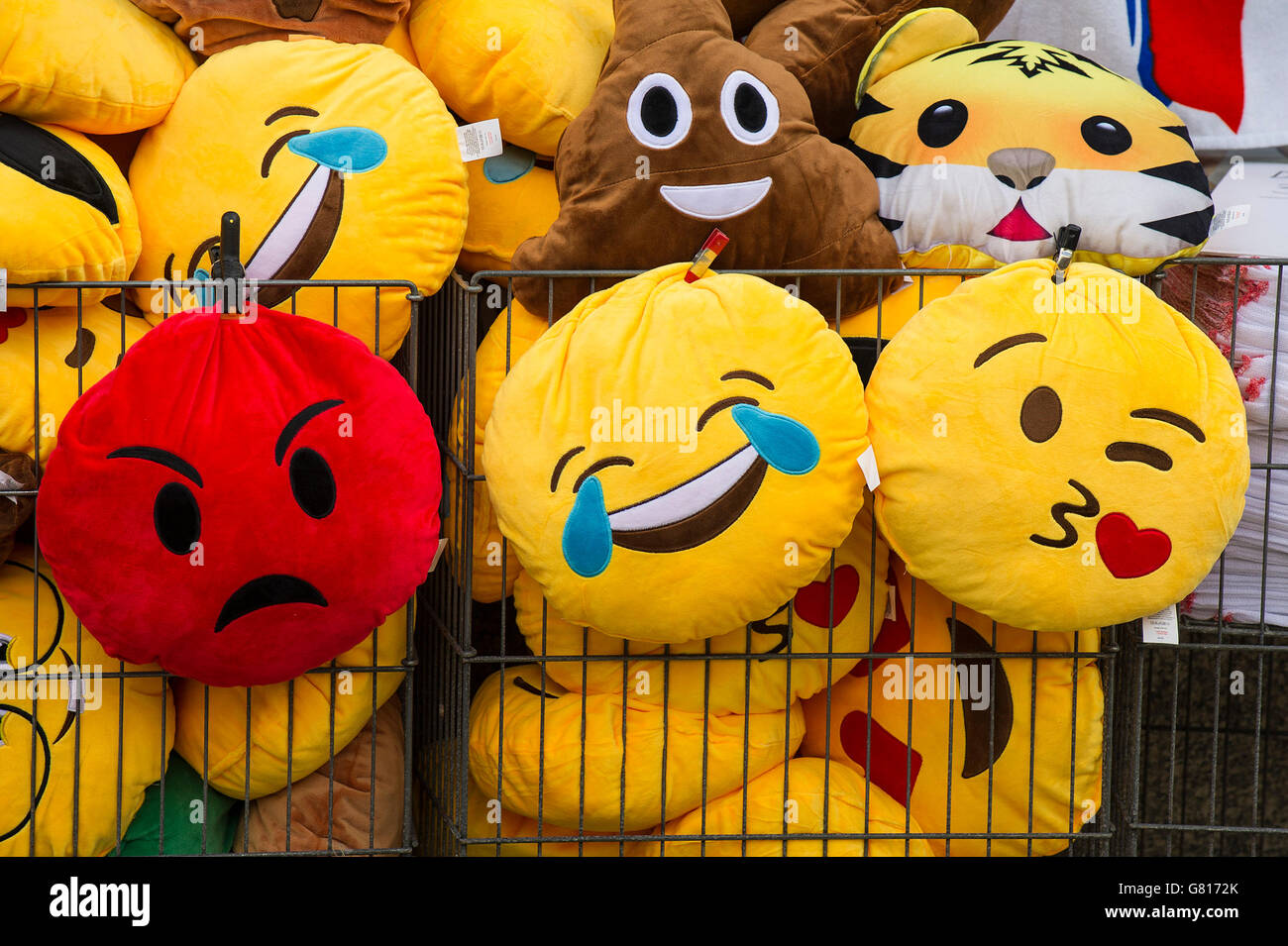 Colourful cushions with embroidered facial expressions. - Stock Image