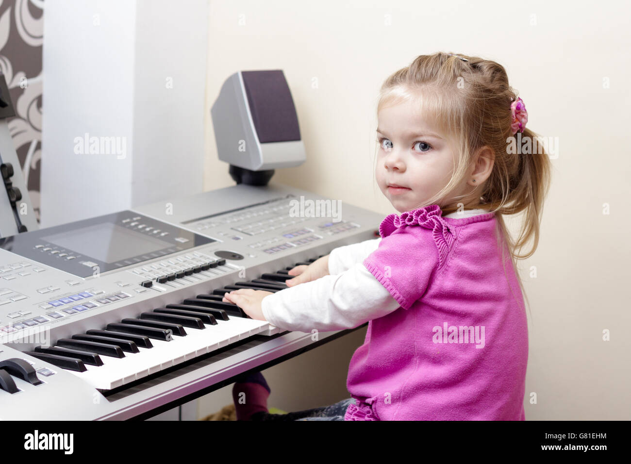 Little cute baby girl playing at synthesizer at home - Stock Image