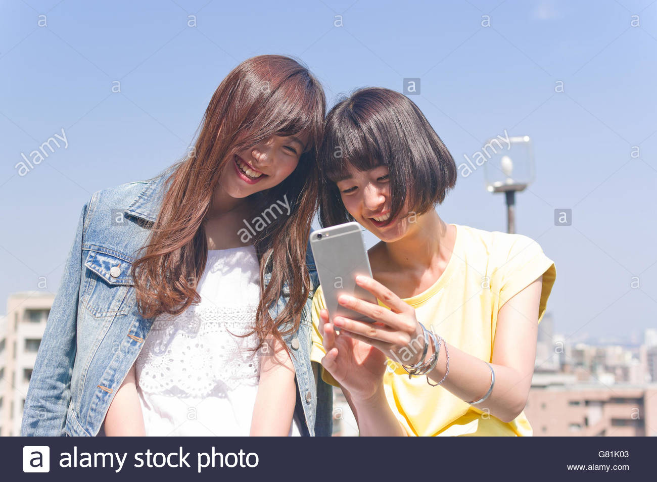 Two women looking into smart phone - Stock Image