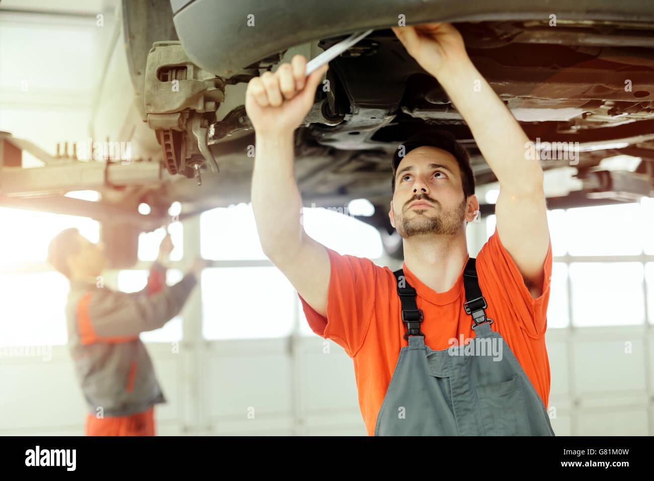 Car mechanic upkeeping car in dealership garage - Stock Image