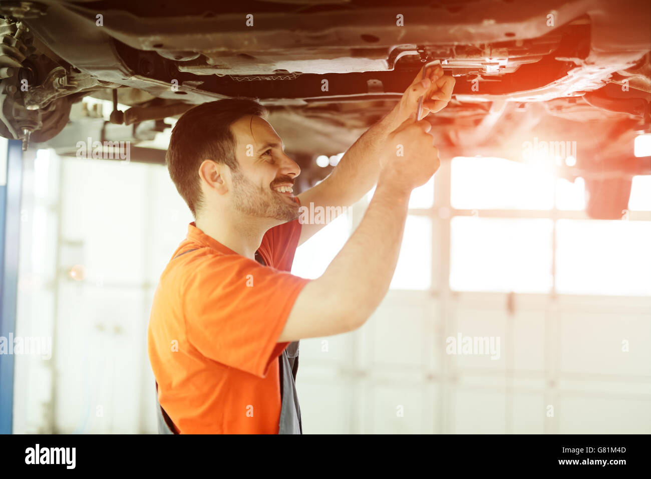 Car mechanic fixing a car in garage at dealership - Stock Image