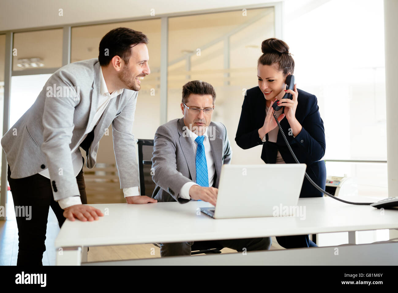 Secretaries assisting boss at business in office - Stock Image