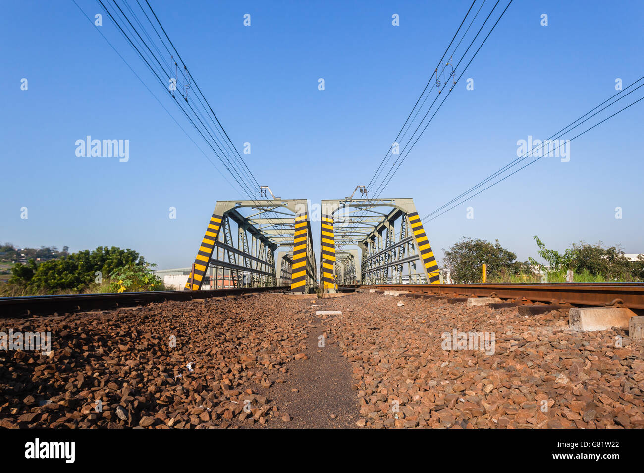 Railway train tracks steel bridge structure at river crossing closeup photo of infrastructure. Stock Photo