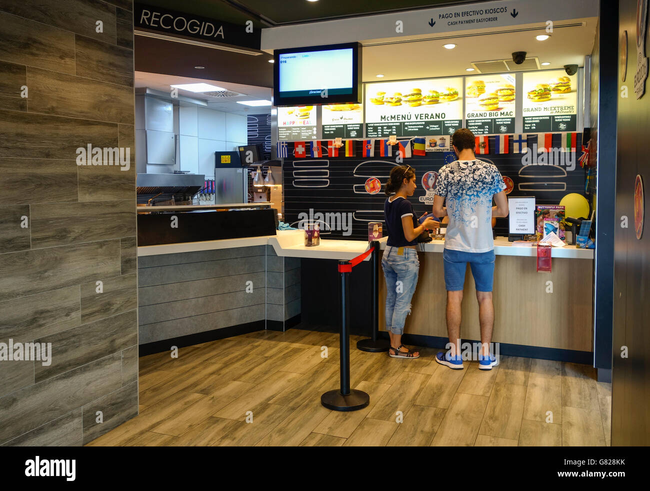 Young couple at counter, Mcdonald's restaurant in Fuengirola, Spain. - Stock Image