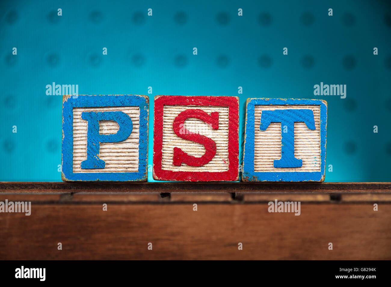 The word 'pst' spelled with letters on wooden toy blocks - Stock Image