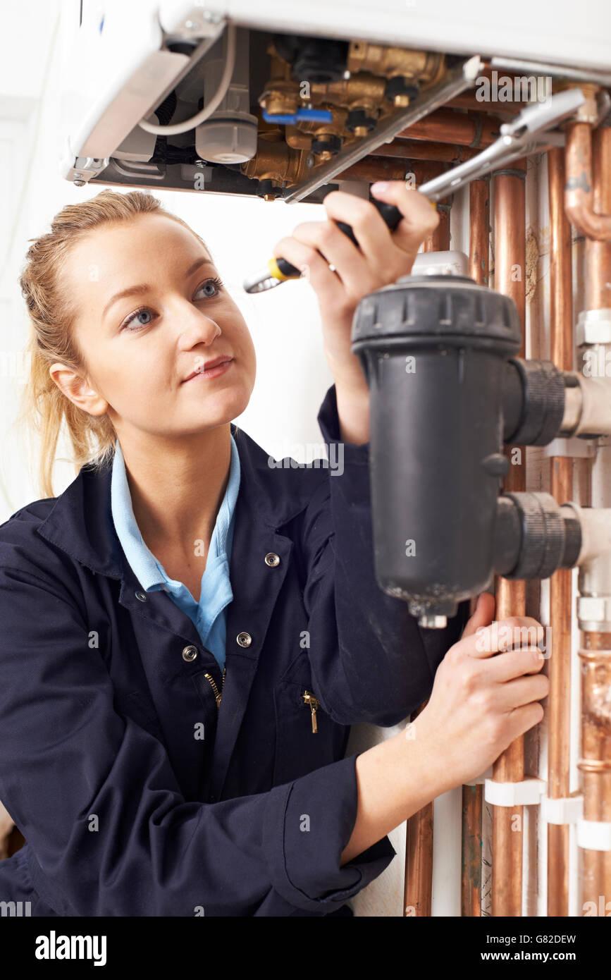Female Plumber Working On Central Heating Boiler - Stock Image