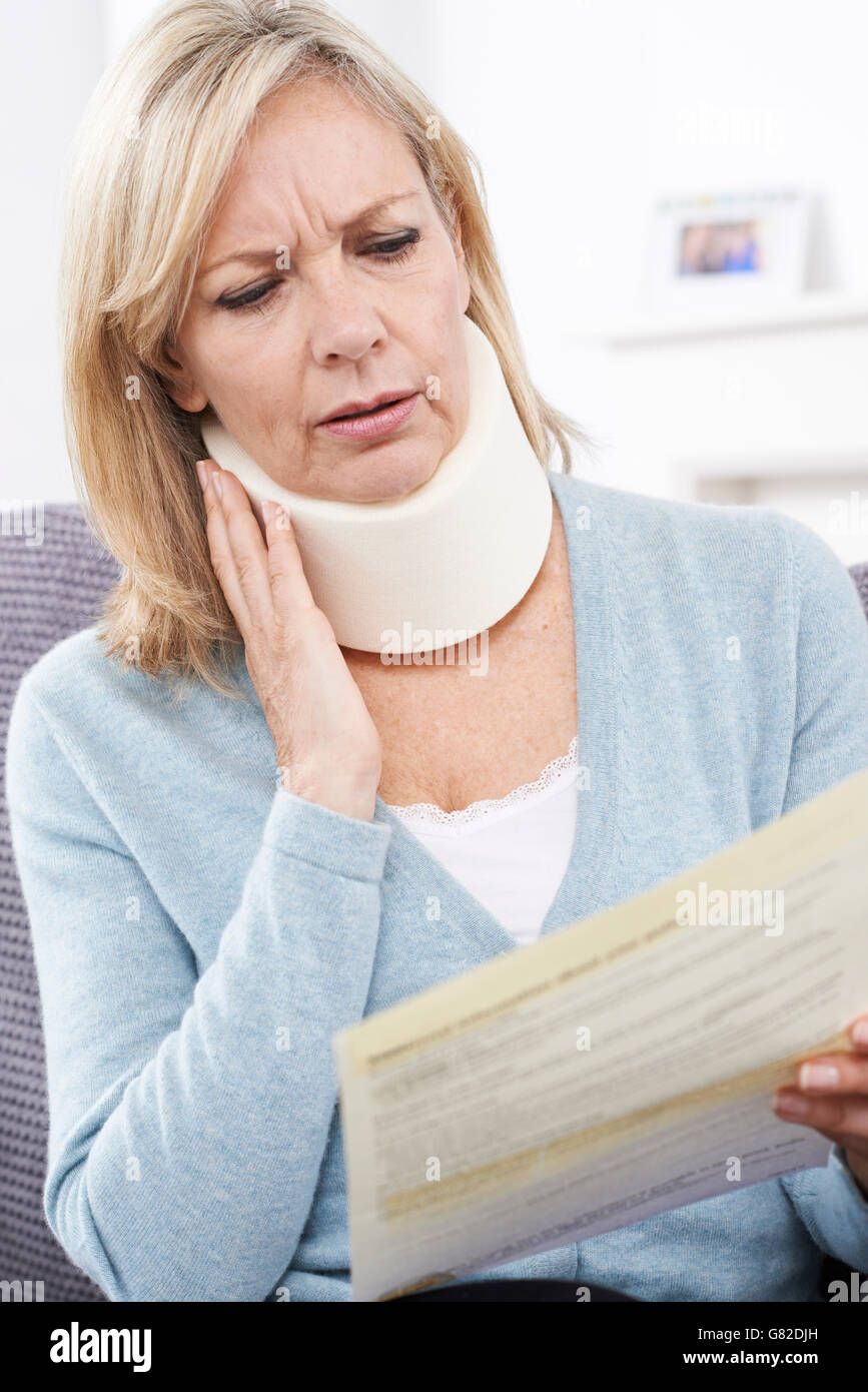 Mature Woman Reading Letter After Receiving Neck Injury - Stock Image